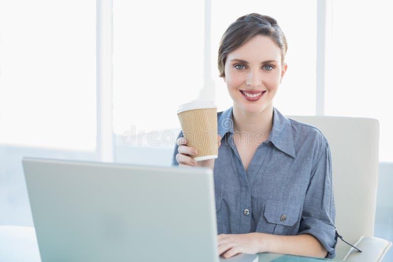 Bella donna di affari calma che mostra tazza eliminabile mentre sedendosi al suo scrittorio fotografia stock libera da diritti
