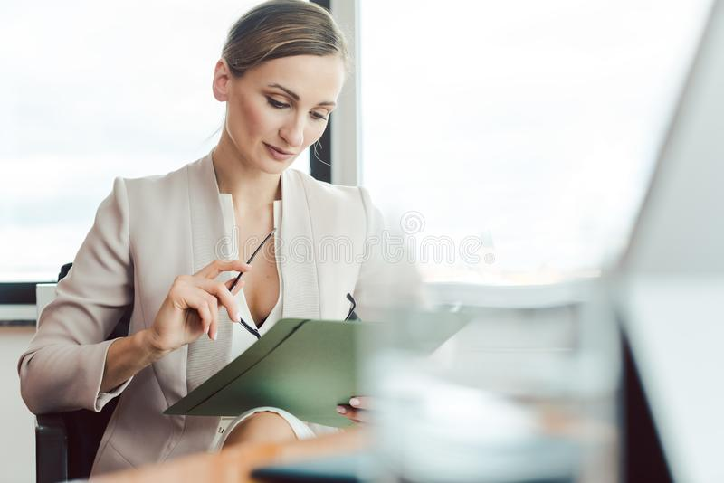 Bella donna di affari che legge un archivio nel suo ufficio immagini stock