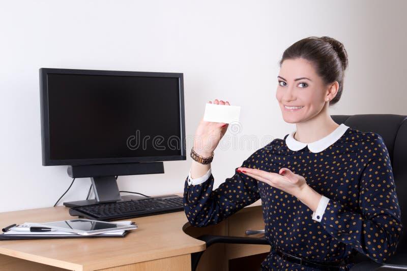 Bella donna di affari che mostra biglietto da visita in ufficio e pc fotografia stock
