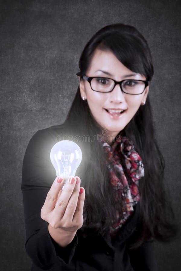 Bella donna di affari che mostra una lampadina luminosa fotografia stock