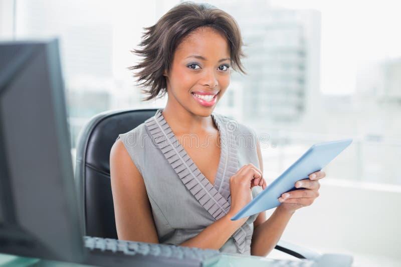 Bella donna di affari che per mezzo del suo pc della compressa e sorridendo alla macchina fotografica fotografia stock libera da diritti