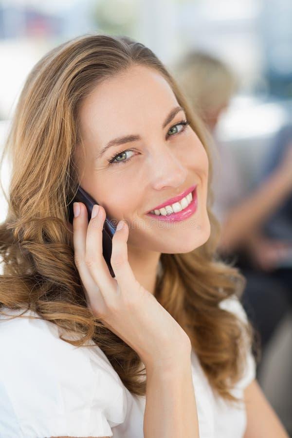 Bella donna di affari che per mezzo del telefono cellulare fotografie stock