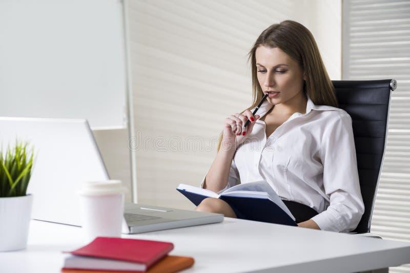 Bella donna di affari che porta una blusa bianca e che si siede al suo scrittorio fotografie stock libere da diritti
