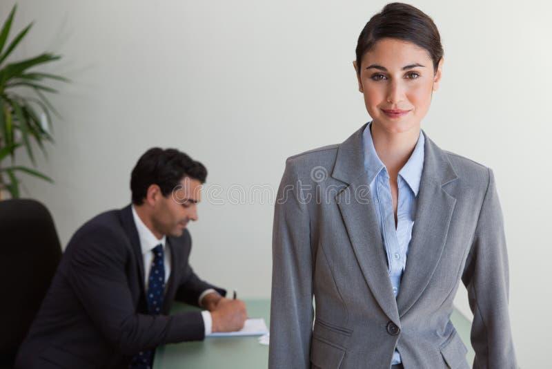 Bella donna di affari che posa mentre il suo collega sta lavorando immagini stock