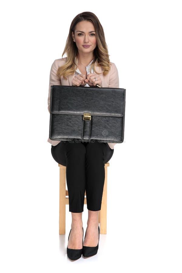 Bella donna di affari che si siede sulla sedia mentre tenendo valigia immagine stock