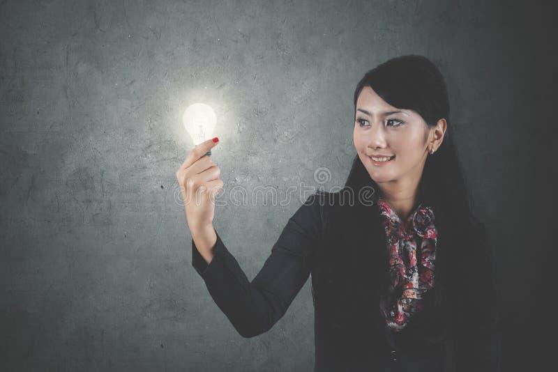 Bella donna di affari che tiene una lampadina luminosa fotografie stock