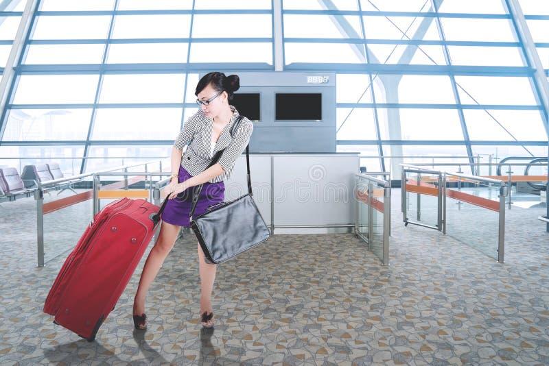 Bella donna di affari che tira una valigia all'aeroporto fotografia stock libera da diritti