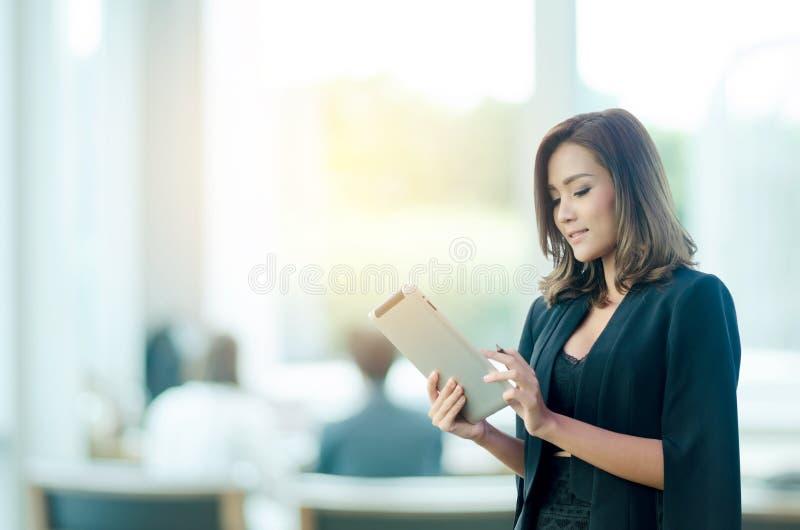 Bella donna di affari che utilizza compressa nell'ufficio fotografia stock