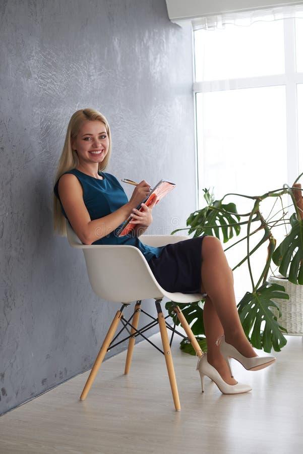 Bella donna di affari con l'archivio sulla sedia dell'ufficio fotografie stock