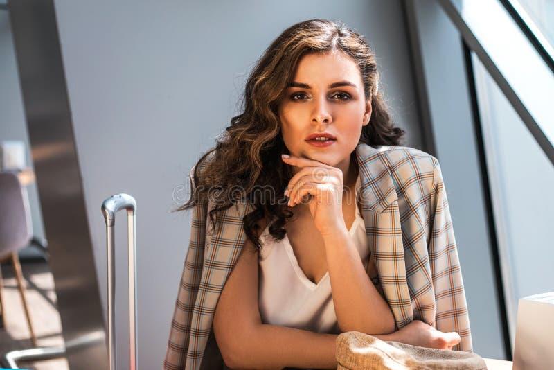 Bella donna di affari con lo smartphone che aspetta il suo volo in un aeroporto immagine stock