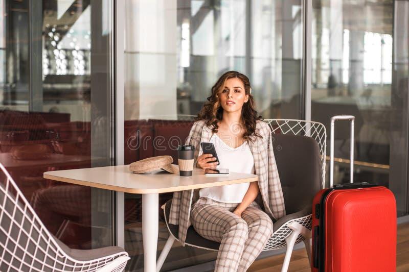 Bella donna di affari con lo smartphone che aspetta il suo volo in un aeroporto fotografie stock