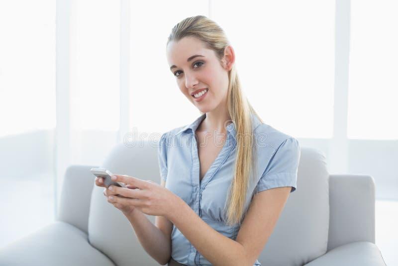 Bella donna di affari contenta che manda un sms con il suo smartphone che si siede sullo strato fotografia stock libera da diritti