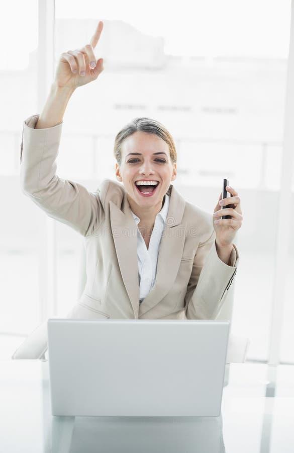 Bella donna di affari contenta che si siede sul suo incoraggiare della poltrona girevole fotografia stock libera da diritti