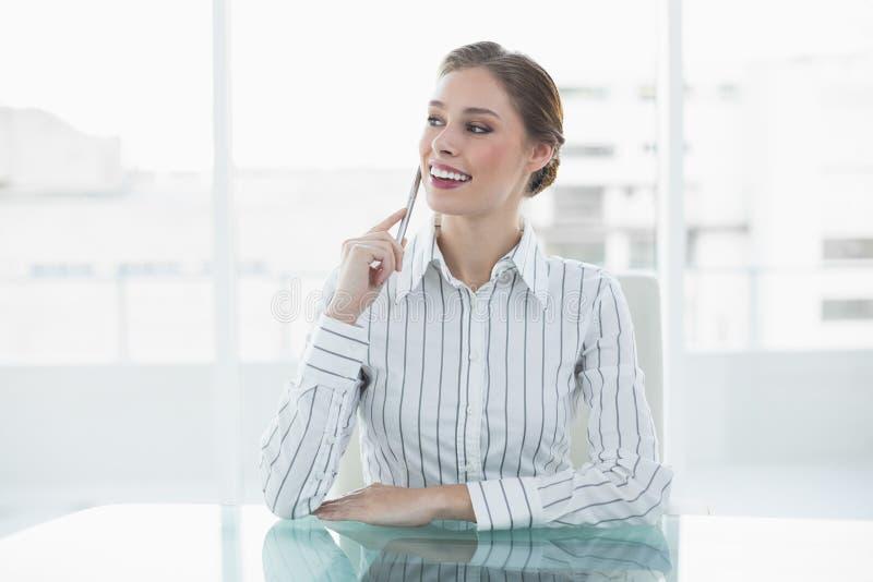 Bella donna di affari di pensiero che si siede al suo scrittorio fotografia stock