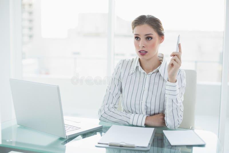 Bella donna di affari di pensiero che tiene una penna che si siede al suo scrittorio fotografia stock libera da diritti