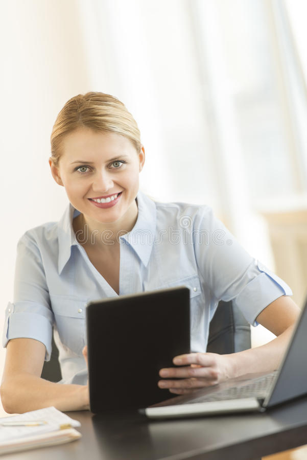 Bella donna di affari With Digital Tablet che si siede allo scrittorio immagine stock libera da diritti
