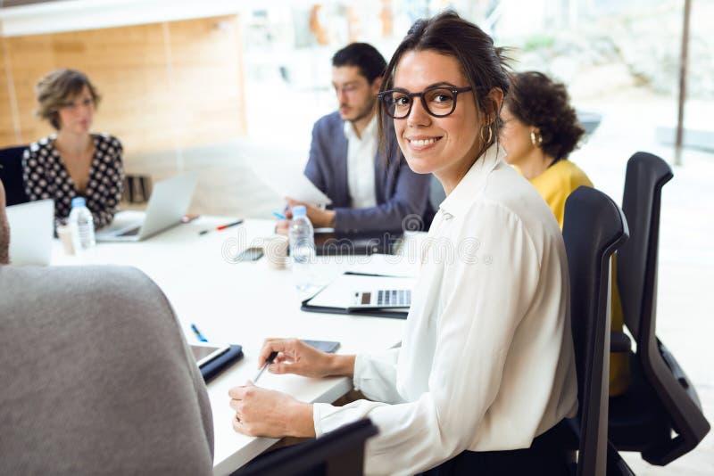 Bella donna di affari elegante che lavora con il computer portatile mentre esaminando macchina fotografica sul posto coworking fotografia stock