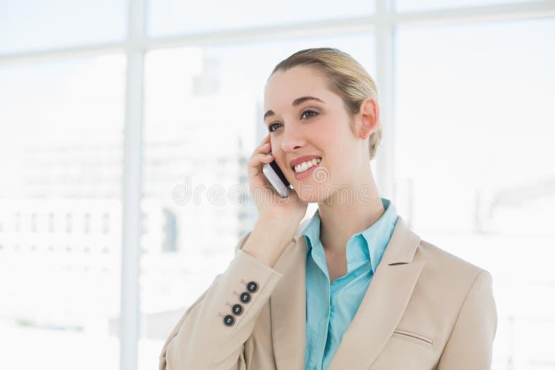 Bella donna di affari elegante che telefona con il suo smartphone fotografia stock