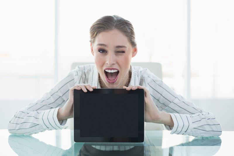Bella donna di affari felice che mostra compressa che lampeggia il suo occhio immagine stock libera da diritti