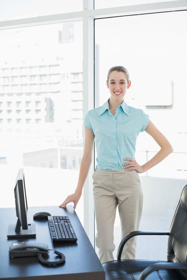 Bella donna di affari felice che posa nel suo ufficio con la mano sull'anca fotografie stock libere da diritti