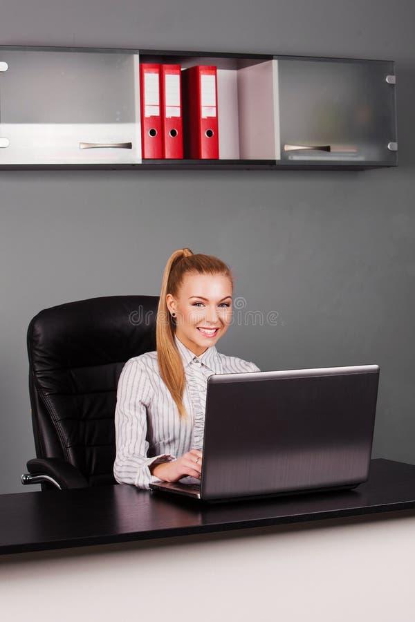 Bella, donna di affari felice che scrive sul computer portatile al suo scrittorio fotografie stock libere da diritti