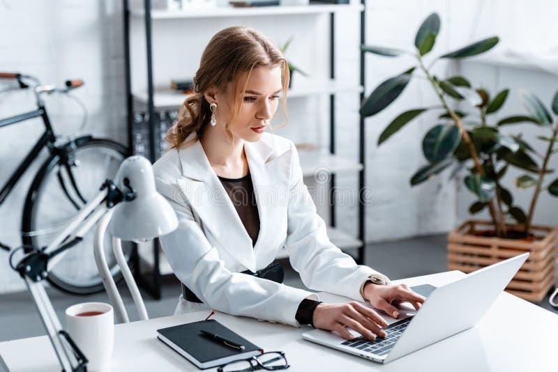 Bella donna di affari messa a fuoco nell'usura convenzionale che si siede allo scrittorio e che scrive sul computer portatile fotografia stock libera da diritti