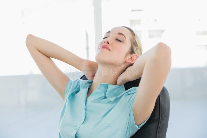 Bella donna di affari pacifica che si rilassa sulla sua poltrona girevole immagine stock