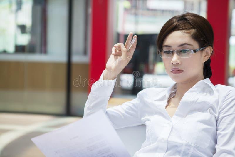 Bella donna di affari pensierosa nel luogo di lavoro immagine stock