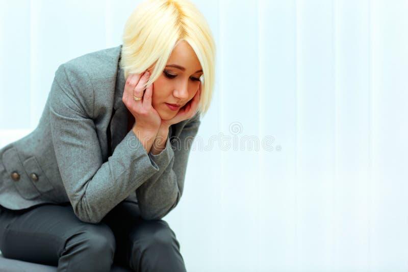 Bella donna di affari premurosa in panno casuale che si siede sulla sedia fotografie stock libere da diritti