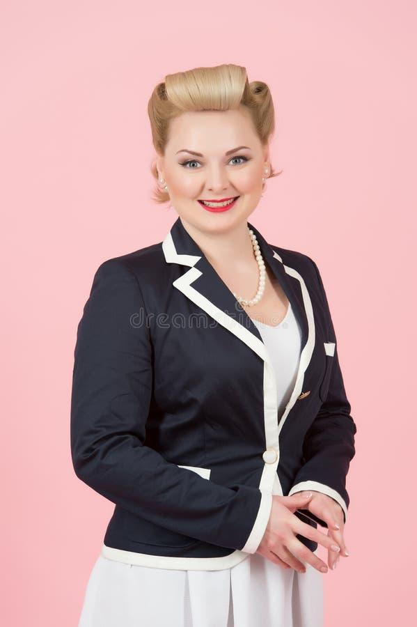 Bella donna di affari in rivestimento con i sorrisi incantanti piacevoli isolato su fondo rosa fotografia stock libera da diritti
