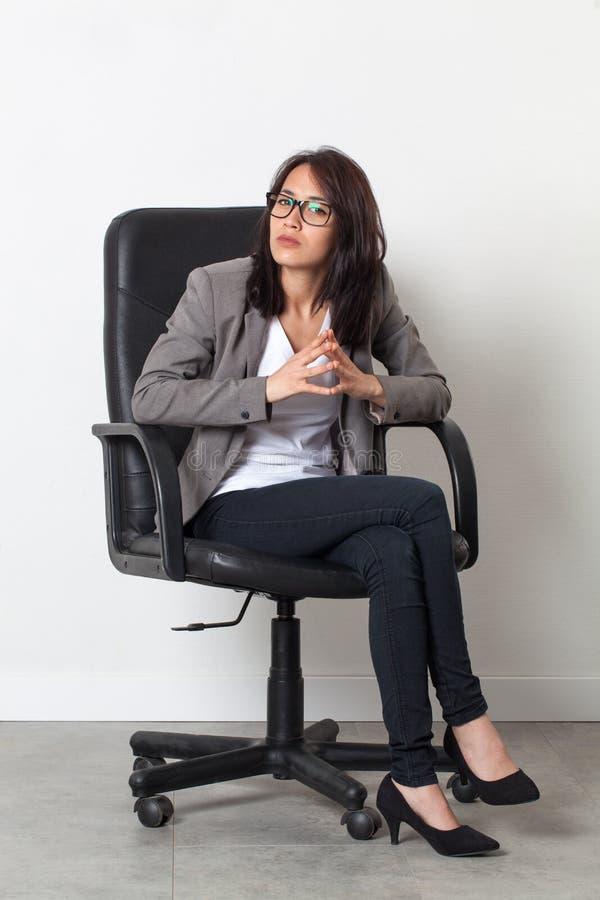 Bella donna di affari seria che si siede per il suo lavoro startup fotografia stock libera da diritti