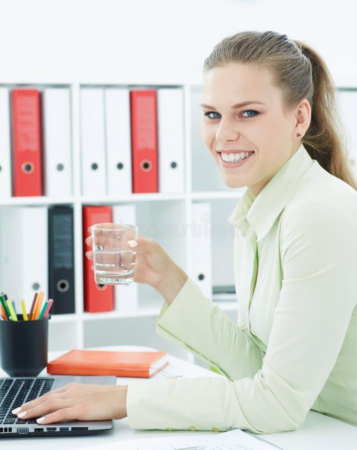 Bella donna di affari sorridente che giudica bicchiere d'acqua disponibile mentre lavorando ad un computer all'ufficio fotografia stock