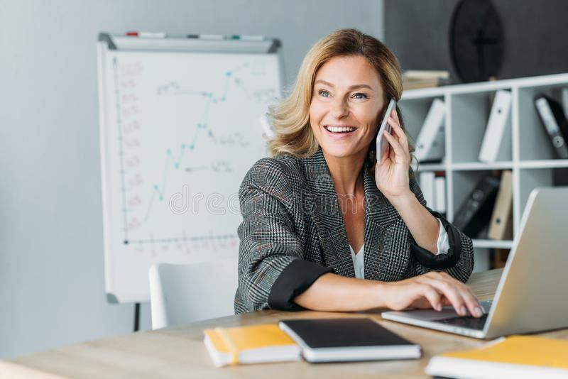 bella donna di affari sorridente che parla dallo smartphone in ufficio fotografia stock libera da diritti