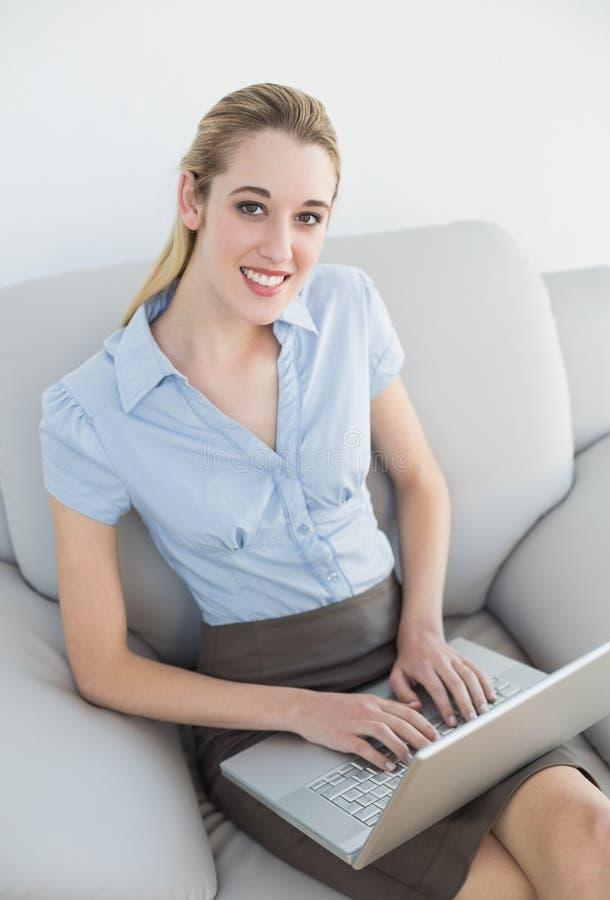 Bella donna di affari sorridente che per mezzo del suo taccuino che si siede sullo strato fotografia stock
