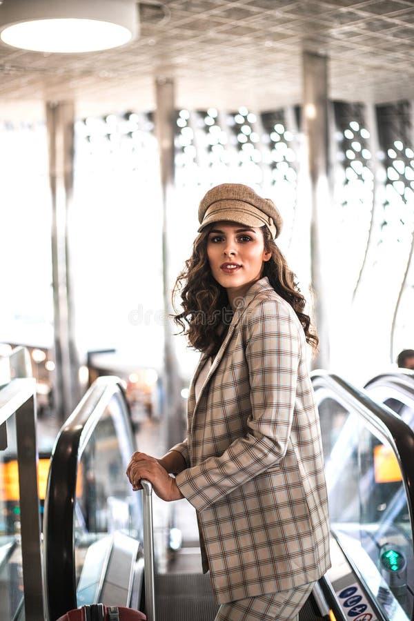 Bella donna di affari sulla scala mobile in aeroporto immagine stock libera da diritti