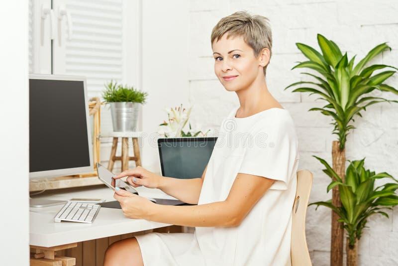 Bella donna di affari in un vestito bianco che si siede ad uno scrittorio ed agli impianti su una compressa fotografia stock