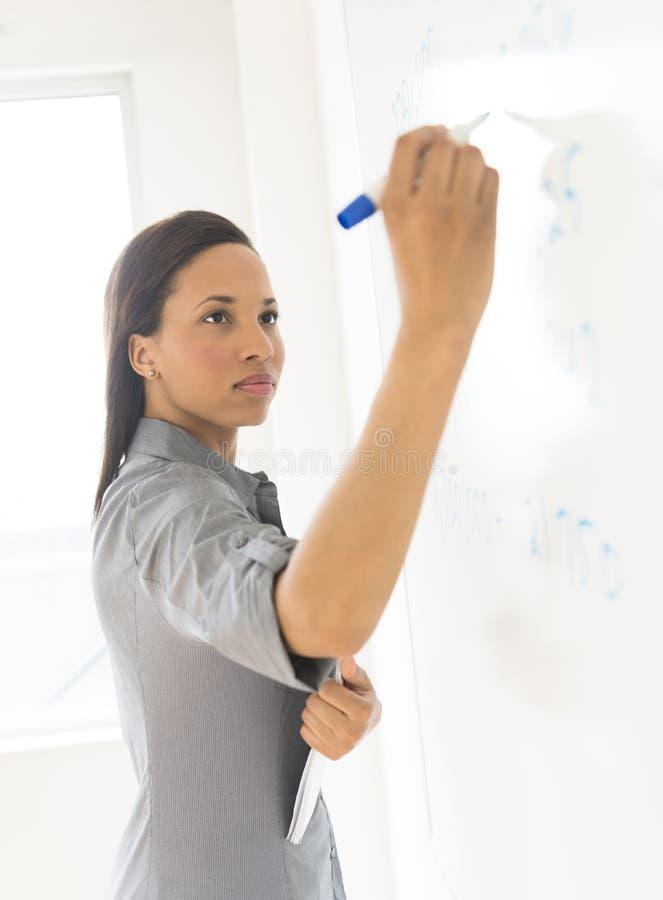 Bella donna di affari Writing On Whiteboard in ufficio immagine stock libera da diritti