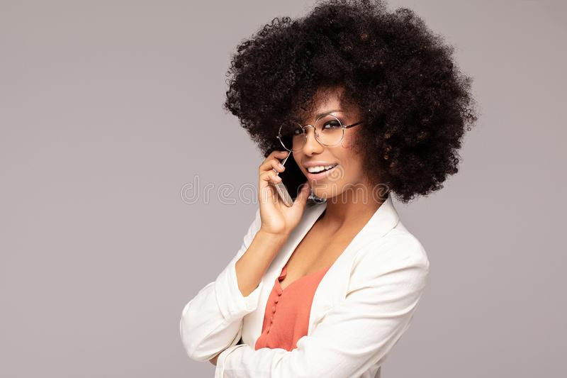 Bella donna di afro che parla dal telefono cellulare immagini stock
