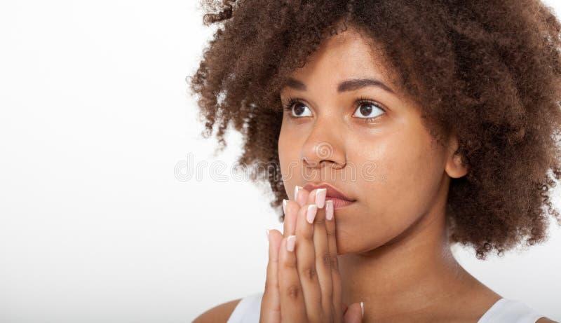 Bella donna di colore che prega insieme, ragazza del ritratto con le sue mani, espressione del primo piano Fede di religione e fotografia stock