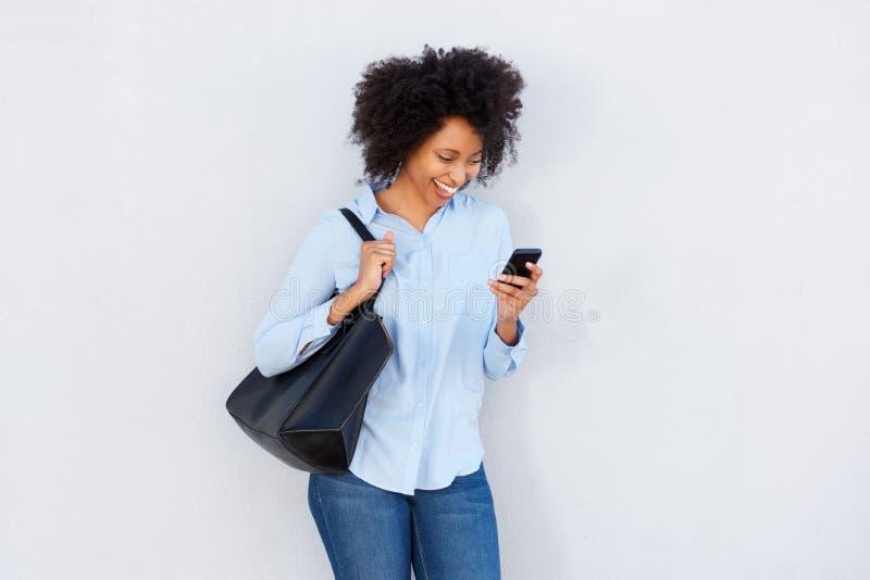 Bella donna di colore con la borsa che esamina cellulare e risata immagine stock