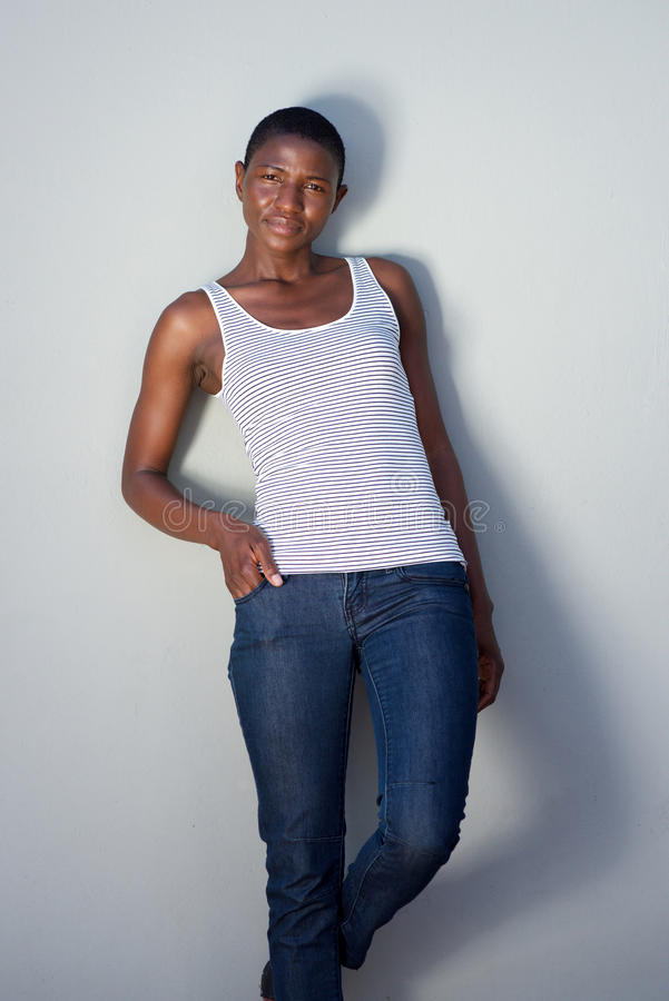 Bella donna di colore d'avanguardia che posa contro la parete immagini stock libere da diritti