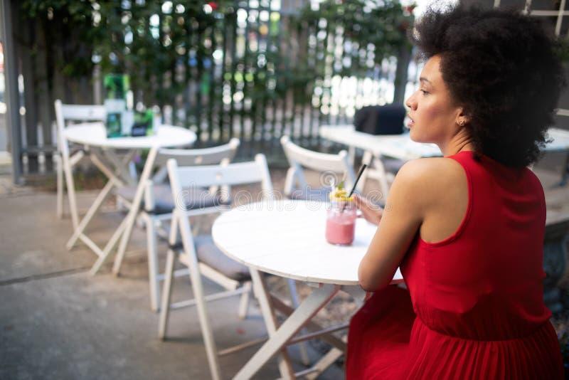 Bella donna di colore felice che beve bevanda e sorridere sani fotografia stock libera da diritti