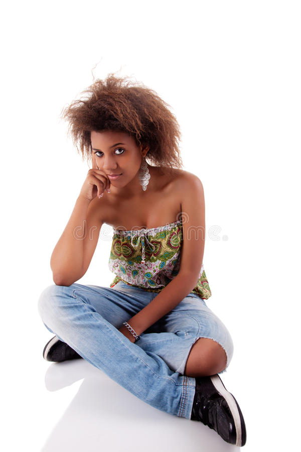 Bella donna di colore, sedentesi sul pavimento immagini stock libere da diritti