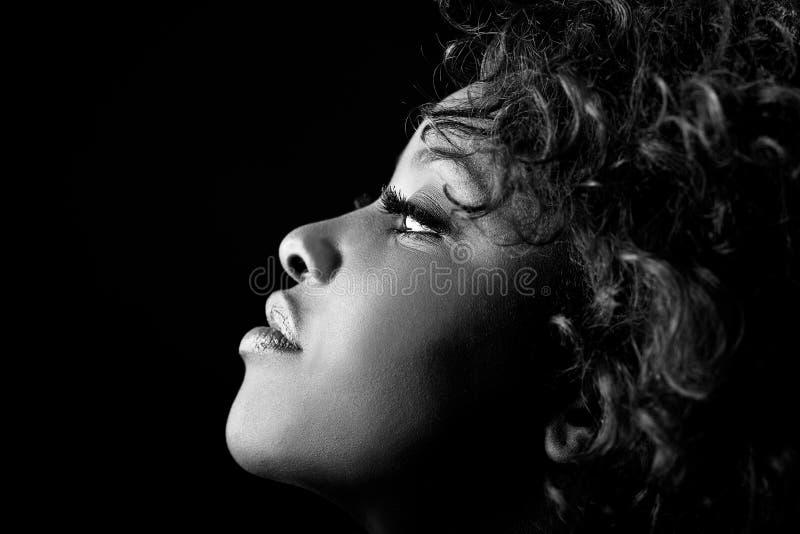 Bella donna di colore su fondo nero. Colpo dello studio immagine stock