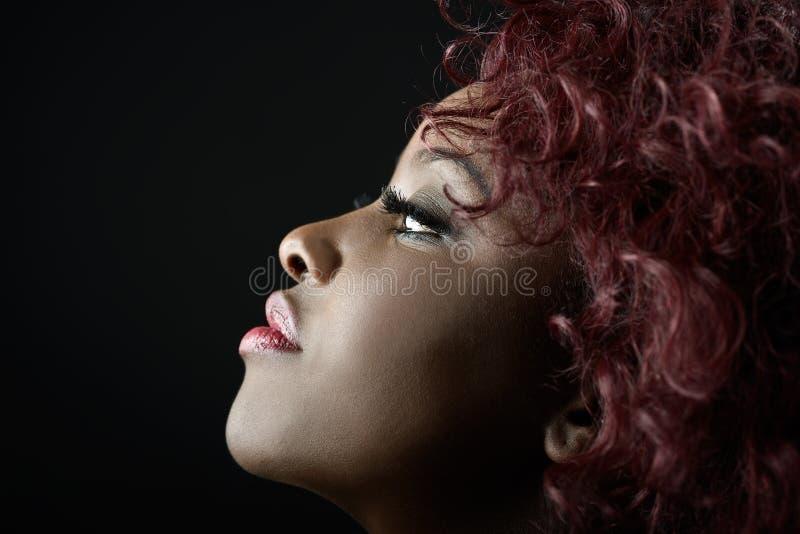 Bella donna di colore su fondo nero. Colpo dello studio fotografia stock