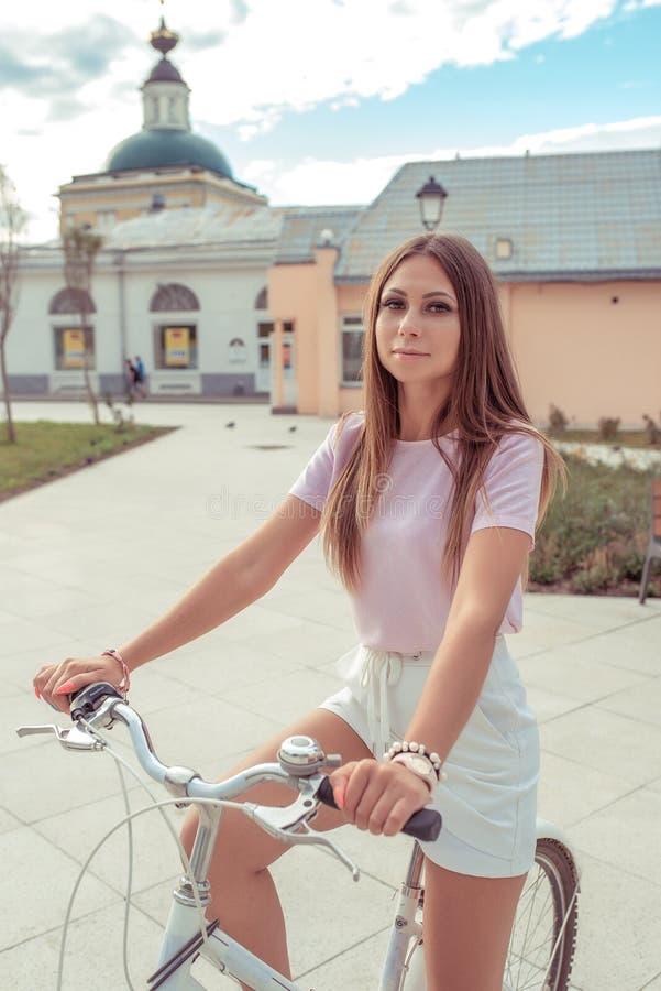 Bella donna di estate in città, stando con una bicicletta, fine settimana di rilassamento, stile di vita attivo, maglietta rosa,  fotografia stock