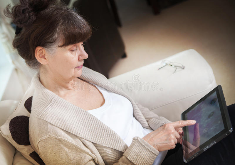 Bella donna di età di pensionamento che cerca in Internet sul dispositivo della compressa immagini stock libere da diritti