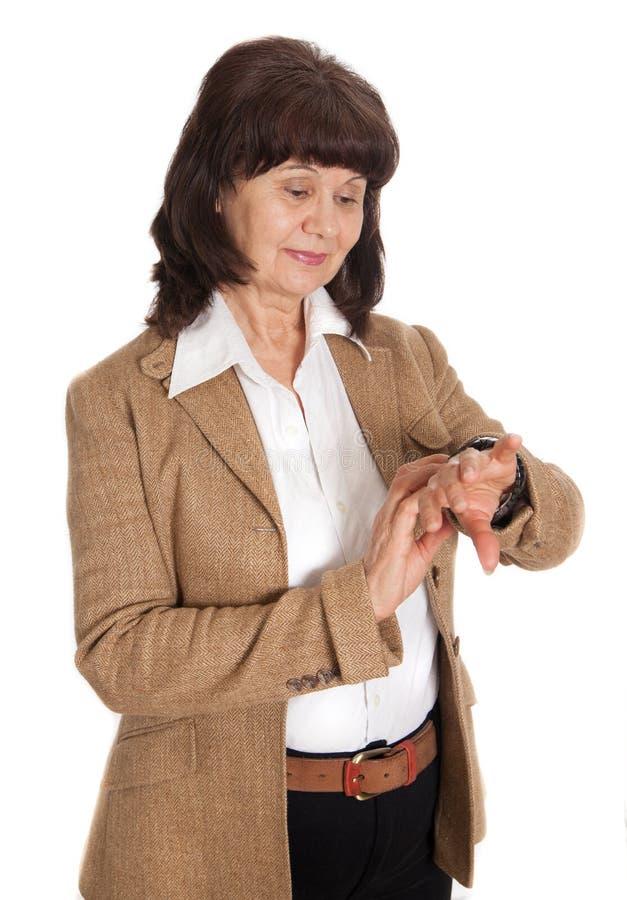 Bella donna di età matura che esamina orologio fotografie stock