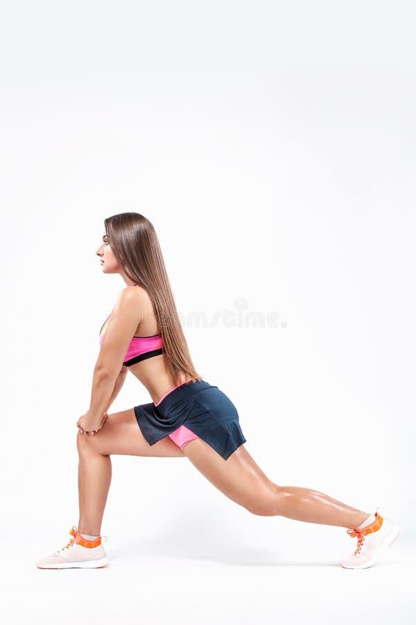 Bella donna di forma fisica in abiti sportivi che fanno allungamento sul pavimento bianco in studio immagini stock libere da diritti