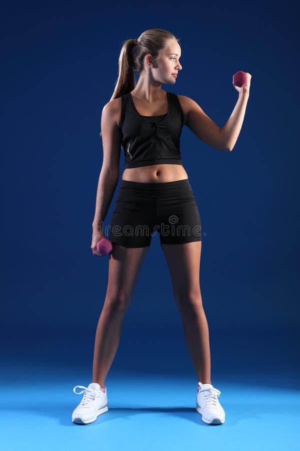 Bella donna di forma fisica che usando i pesi di esercitazione immagine stock libera da diritti